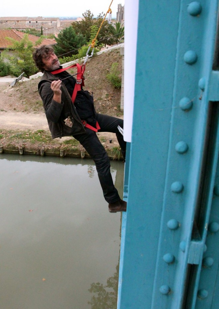 Gauthier hangs panels on the bridge in Capestang, painting, bringing awareness to the plight of the planes